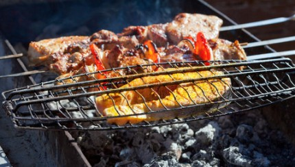 Juicy slices of meat and fish with sauce prepare on fire.